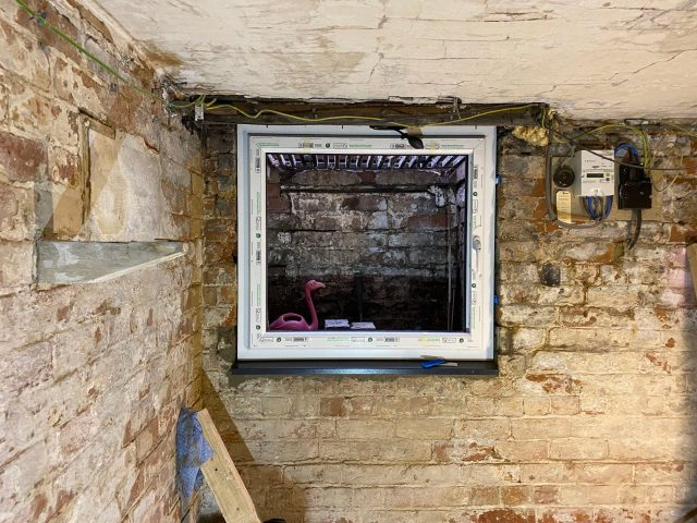 fitting a window in a cellar or basement
